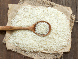 Basmati rice with a spoon on an dark wood